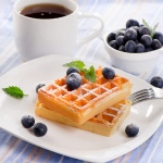 French waffles with blueberries and hot coffee