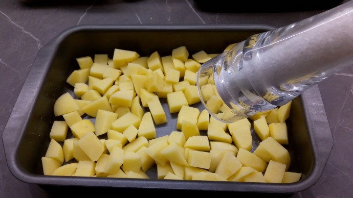Chopped potatoes in oven tray